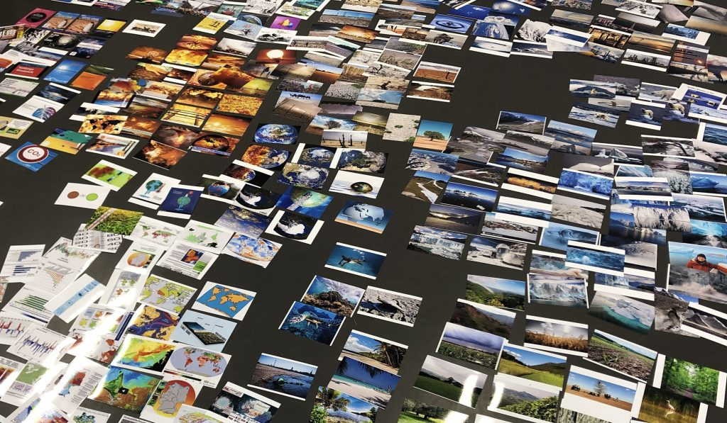 """Klimabilder im Netz. Fotografische Abzüge von Suchergebnissen der Google-Bildersuche, sortiert durch die Mitarbeiter:innen des Forschungsprojekts """"Networked Images of Climate Change. Foto: Birgit Schneider"""